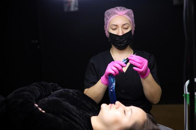 El tatuador prepara el aparato de tatuaje para el procedimiento.