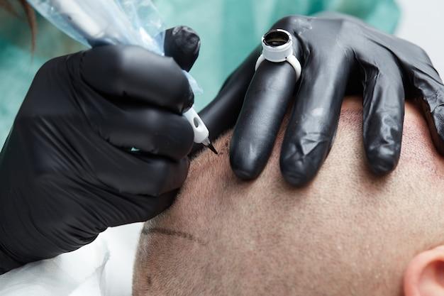 Tatuador profesional haciendo tricopigmentación de maquillaje permanente