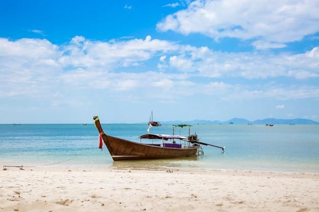 Taxi asiático barco de cola larga en una playa tropical de arena blanca, cielo azul y montañas marinas en el horizonte