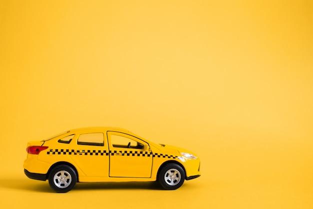 Taxi urbano y concepto de servicio de entrega. modelo de coche de taxi amarillo de juguete