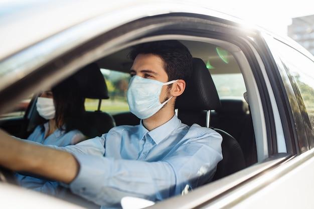 El taxista joven lleva una máscara médica estéril en el coche. concepto de pandemia de coronavirus.