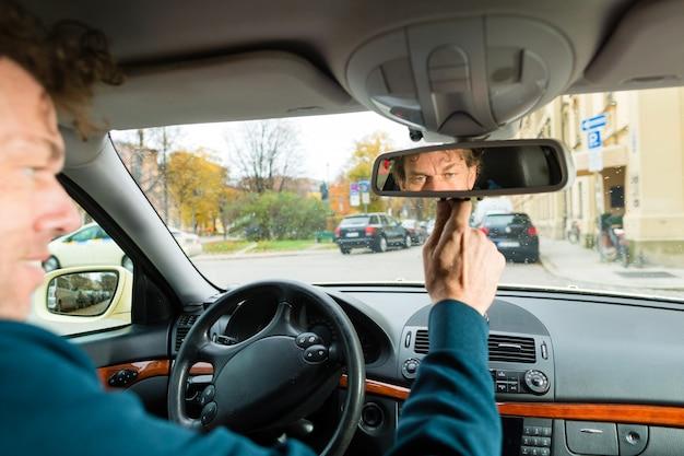 Taxista está mirando en el espejo de conducción