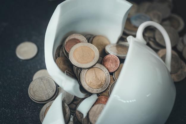 La taza acaba de romperse en pedazos y el dinero de la moneda está tirado a su alrededor.