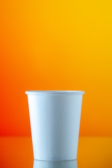Taza de agua de papel vista frontal en pared naranja