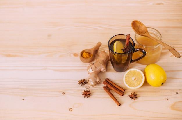 Taza de agua tibia con limón, miel, jengibre, canela y anís.