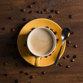 Taza amarilla con bebida cerca de granos de café