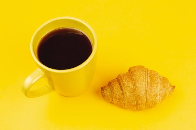Taza amarilla con café y croissant sobre un fondo amarillo