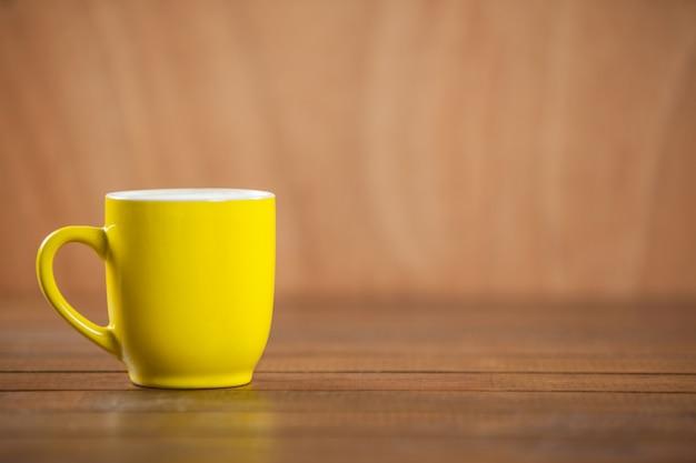 Taza amarilla de café en la mesa de madera