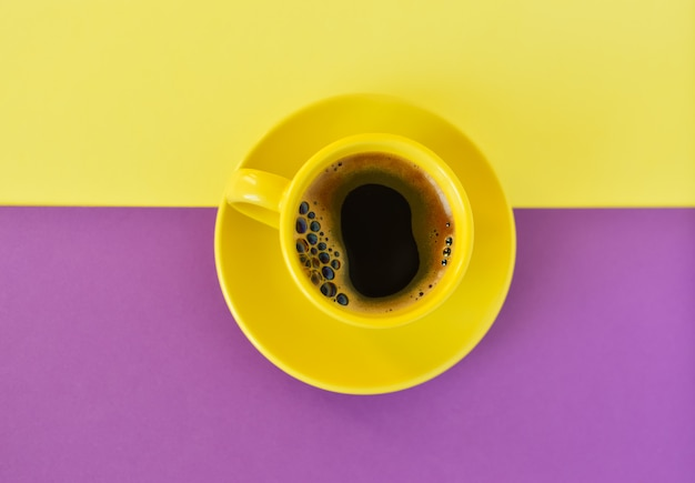 Taza amarilla con café sobre un fondo amarillo y violeta doble