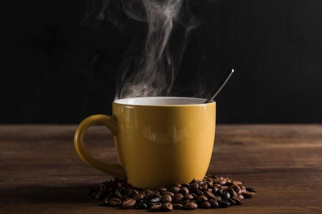 Taza amarilla con cuchara y granos de café.