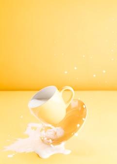 Taza amarilla flotando con leche derramando