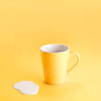 Taza amarilla con leche derramada