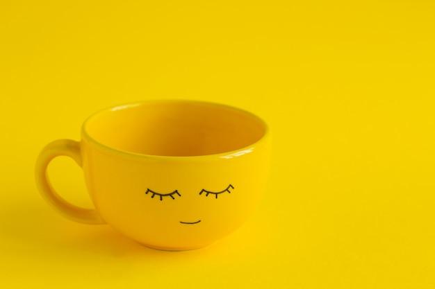 Taza amarilla con linda sonrisa cara en amarillo