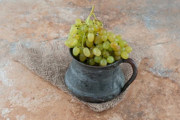 Una taza antigua llena de uvas dulces en la mesa de mármol.