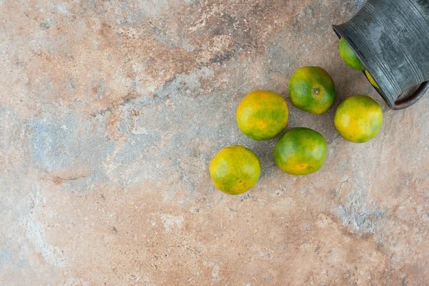 Una taza antigua con mandarinas ácidas sobre mesa de mármol.