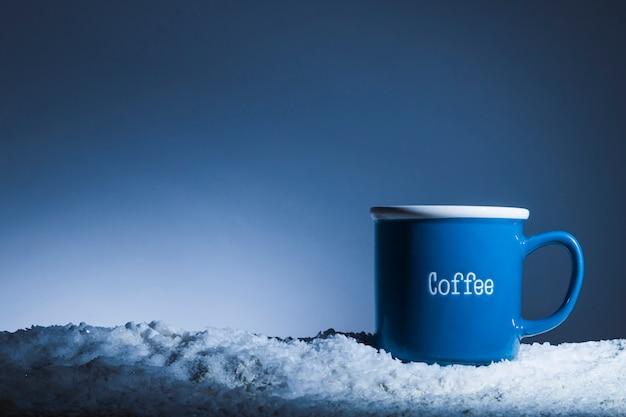 Taza azul en banco de nieve