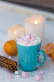 Taza azul de bebida con crema batida y malvaviscos
