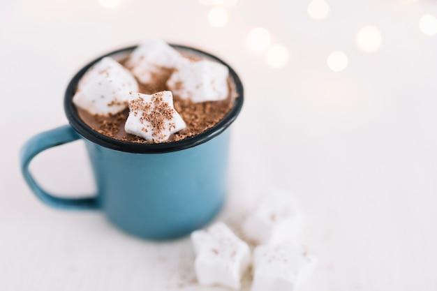 Taza azul con cacao y malvaviscos suaves.