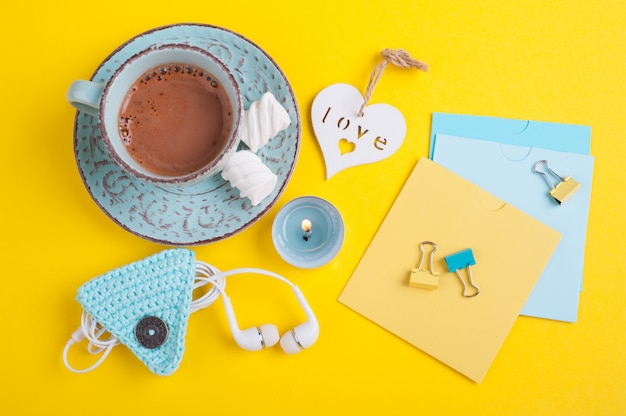 Taza azul de chocolate caliente y notas en blanco