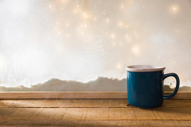 Taza azul en la mesa de madera cerca del banco de nieve y luces de hadas