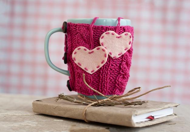 Taza azul en un suéter rosa de pie sobre un viejo cuaderno