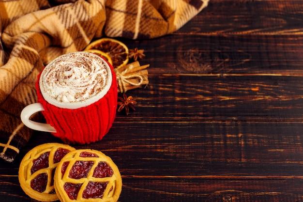 Una taza de bebida caliente con crema batida y polvo, en una funda de punto y galletas y especias caseras.