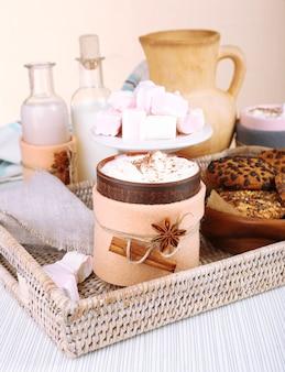 Taza de bebida caliente decorada en fieltro sobre mesa de madera