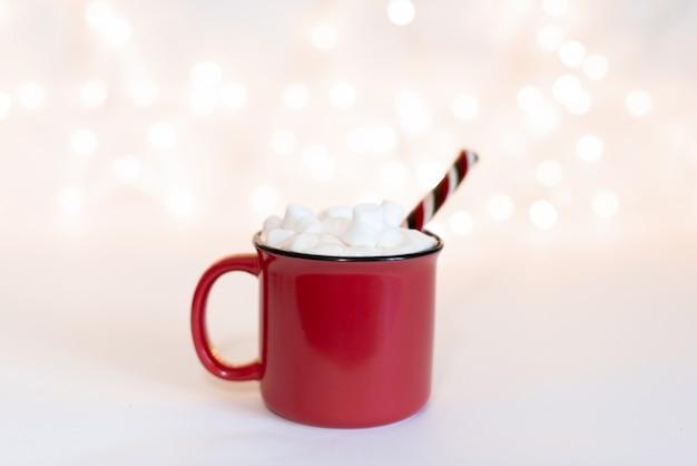 Taza con bebida caliente y galletas navideñas