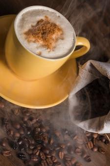 Taza con bebida caliente y granos de café esparcidos del saco.