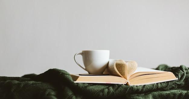 Una taza de bebida caliente y un libro con páginas dobladas en un corazón sobre una acogedora manta tejida.