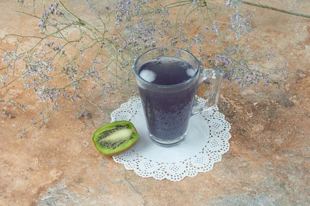 Una taza de bebida deliciosa con una rodaja de kiwi en la mesa de mármol.