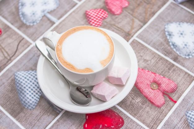 La taza de bebida energética de la mañana dulce está de pie sobre un mantel con un patrón en forma de corazones