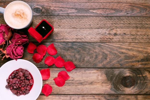 Taza de bebida, flores, mermelada, pétalos y anillo en caja de regalo.