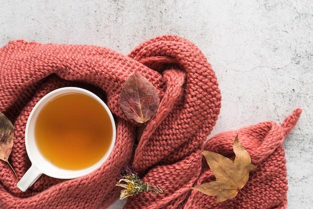 Taza con bebida en géneros de punto y hojas