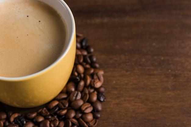 Taza con bebida y granos de café.