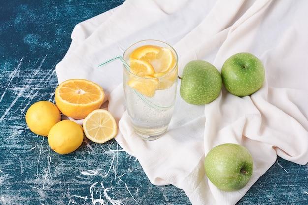 Una taza de bebida con limón sobre azul.