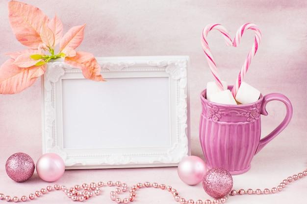 Taza de bebida, malvaviscos, dulces en un palo, flor de pascua rosa y marco de fotos