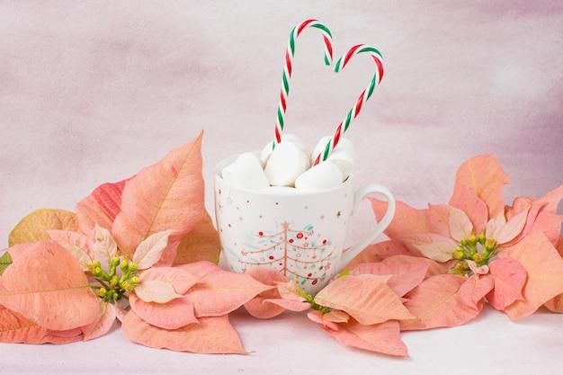 En una taza de bebida, malvaviscos, dulces en un palo, flor de pascua rosa