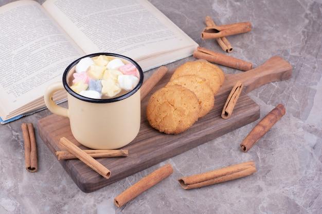Una taza de bebida con malvaviscos y galletas de avena.