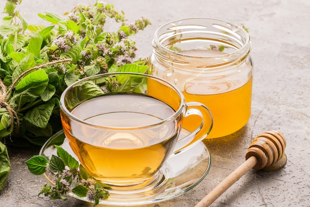 Taza de bebida de té con hojas frescas de menta, melisa y miel gris
