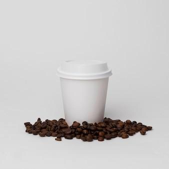 Taza blanca en arreglo de granos de café