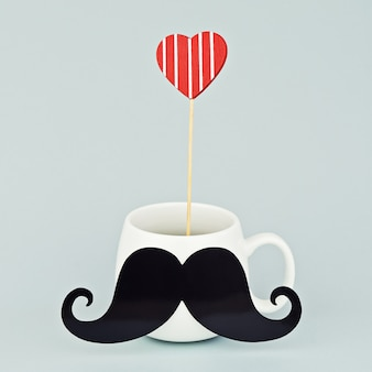 Taza blanca con bigote negro y corazón rojo.