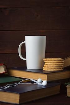 Taza blanca con café caliente, galletas y auriculares en libros desplegados en una pared de madera oscura