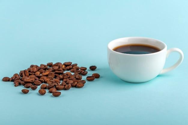 Taza blanca con café espresso negro y montón de granos de café sobre fondo azul.