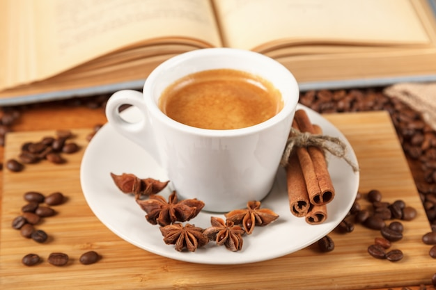 Taza blanca de café espresso rodeada de granos de café tostados