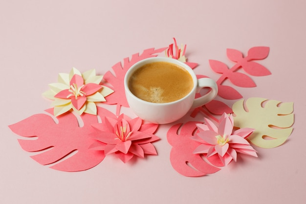 Taza blanca de café espresso sobre un fondo rosa pastel con papel de origami moderno