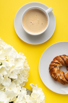 Taza blanca de café y flores sobre fondo amarillo. concepto de desayuno de vista superior plana endecha