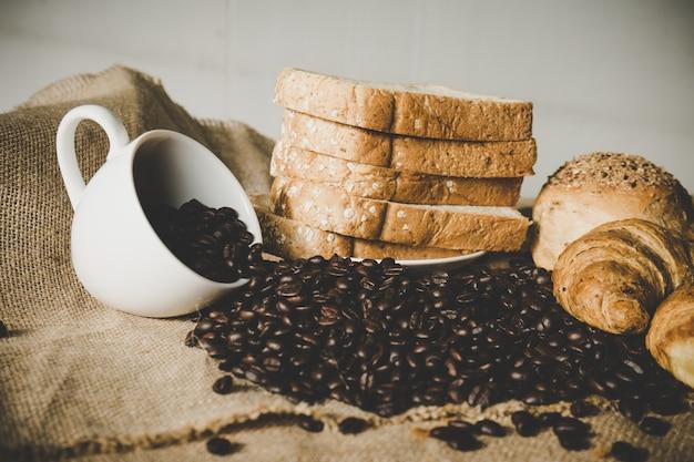 Taza blanca de café de frijoles con croissant y pan