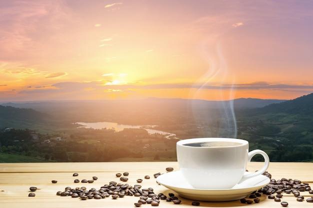 Taza blanca de café y granos de café en la tabla de madera con el fondo de la puesta del sol natural