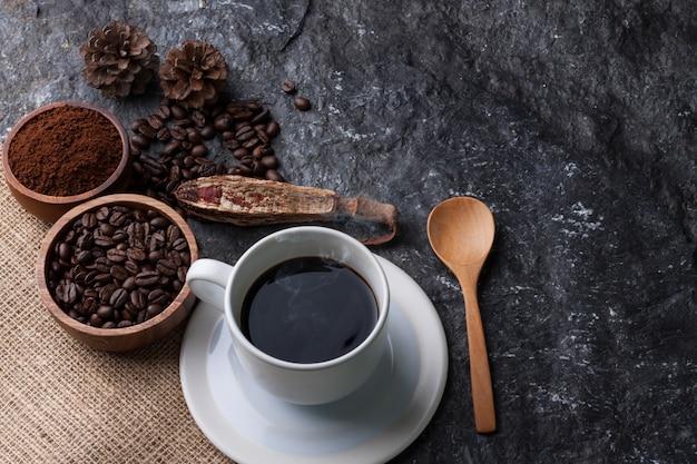 Taza blanca de café, granos de café en una taza de madera sobre arpillera, cuchara de madera sobre fondo de piedra negra